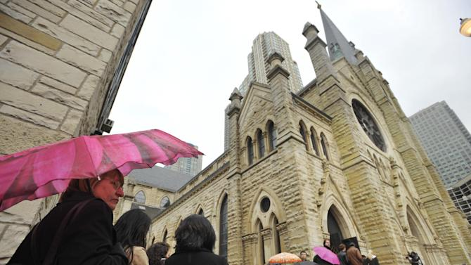 Mourners line up in the rain to attend film critic Roger Ebert's funeral at Holy Name Cathedral in Chicago, Monday, April 8, 2013. The Pulitzer Prize winning movie reviewer died Thursday, April 4 at age 70 after a long battle with cancer. (AP Photo/Paul Beaty)