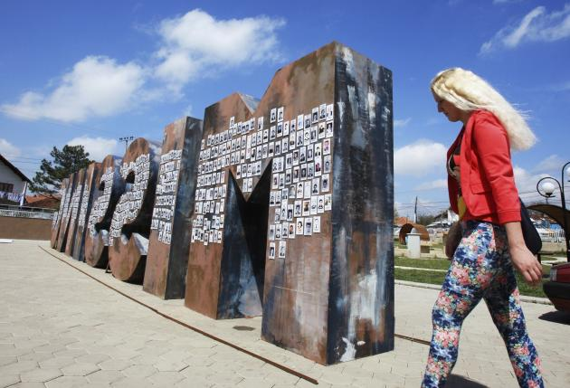 "A Kosovar Serbian woman walks near the ""Missing"" monument covered with pictures of missing Serbs, in Gracanica near the capital Pristina"