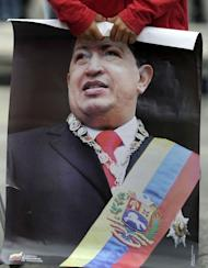 A boy holds a poster of Venezuelan President Hugo Chavez as the leader's supporters gather at Simon Bolivar Square in Caracas on February 18, 2013. Even as passionate supporters took to the streets in noisy celebration, and foreign dignitaries sent congratulations and urged Chavez to rest, the next step for the oil-rich country and its colorful leader remained unclear