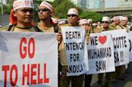 Indonesian members of the Justice and Prosperity Party hold banners during a protest against a low-budget American film insulting to Muslims outside the US embassy in Jakarta. As protests again erupted across the Muslim world on Wednesday over the film, a French magazine poured fuel on the fire by publishing obscene cartoons depicting the Prophet Mohammed
