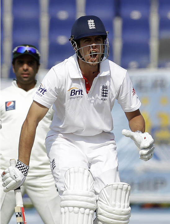 England's Alastair Cook, right, reacts after playing a shot during the second day of the second cricket test match of a three match series between England and Pakistan at the  Zayed Cricket Stadium in