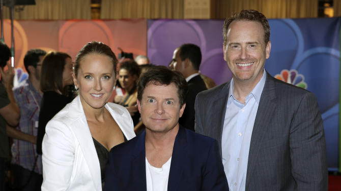 """This image released by NBC shows, NBC Entertainment President Jennifer Salke, left, and Entertainment Chairman Robert Greenblatt, right, with actor Michael J. Fox during the Television Critics Association summer press tour in Beverly Hills, Calif., on Saturday, July 27, 2013. Fox will star in """"The Michael J. Fox Show,"""" as Mike Henry, a former local NBC newscaster with Parkinson's. (AP Photo/NBC, Paul Drinkwater)"""