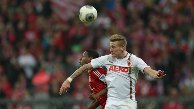 Bayern's David Alaba of Austria, background left, and Augsburg's Andre Hahn challenge for the ball during the German first division Bundesliga soccer match between FC Bayern Munich and FC Augsburg, in Munich, southern Germany, Saturday, Nov. 9 2013