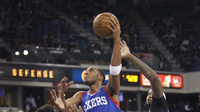 Philadelphia 76ers forward Evan Turner (12) shoots over Sacramento Kings defenders Ben McLemore (16) and DeMarcus Cousins (15) during the first half of an NBA basketball game in Sacramento, Calif., on Thursday, Jan. 2, 2014