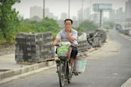 A man covers his nose against the stench rising from a garbage dump as he rides on his motorcycle in the Songjiang district of Shanghai. When the wind blows, residents can smell the stench rising from the garbage dump, feared to be so harmful it can make people vomit and cause birth defects