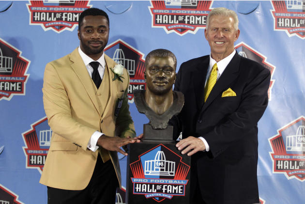 Former NFL player Curtis Martin, left, poses with a bust of himself and his presenter, his former coach Bill Parcells, during an induction ceremony at the Pro Football Hall of Fame, Saturday, Aug. 4,