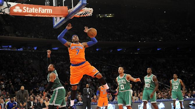New York Knicks' Carmelo Anthony (7) dunks a basket as Boston Celtics' Jared Sullinger (7), Avery Bradley (0), Brandon Bass (30) and Jordan Crawford (27) watch from behind during the first half of an NBA basketball game on Sunday, Dec. 8, 2013, in New York. The Celtics won 114-73