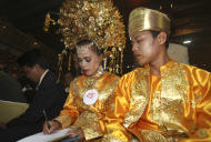 An Indonesian couple signs a wedding letter during a mass wedding ceremony in Jakarta, Indonesia, Tuesday, July 19, 2011. Thousands of underprivileged Indonesian couples from various faiths joined a reception to commemorate their mass wedding. (AP Photo/Achmad Ibrahim)