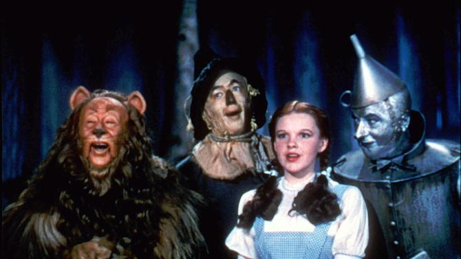 "FILE - In this undated file photo provided by Warner Bros., Bert Lahr as the Cowardly Lion, Ray Bolger as the Scarecrow, Judy Garland as Dorothy, and Jack Haley as the Tin Woodman, sing in this scene from ""The Wizard of Oz,"" distributed by Warner Bros. On Sunday, Nov. 11, 2012, auction house Julien's Auctions said the blue pinafore dress that Garland wore in the movie fetched the highest price of any item during a two-day auction of Hollywood memorabilia that attracted bids from around the world, selling for $480,000. (AP Photo/Warner Bros., File) NO SALES"