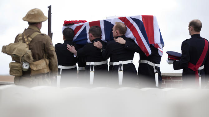 A man dressed as a World War One soldier watches as the casket of a World War One soldier is carried during a ceremony at the H.A.C. cemetery in Ecoust-St-Mein, France on Tuesday, April 23, 2013. Almost 100 years after they were killed in action, Lieutenant John Harold Pritchard and Private Christopher Douglas Elphick were re-interred with full military honors in a private ceremony. Lieutenant Pritchard was killed in action on May 15, 1917 during an enemy attack near Bullecourt, France and his remains were found in a field near the site in 2009. His body was eventually identified by a silver bracelet with his name engraved on it. Private Elphick was born in Dulwich, South London in 1889. He was killed in action on May 15, 1917 during an enemy attack near Bullecourt, France and his remains were found in a field near the site in 2009. His body was eventually identified by a signet ring bearing his initials. (AP Photo/Virginia Mayo)