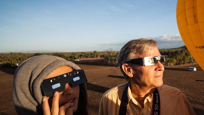 """In this photo released by Hot Air Balloon Cairns, Hank Harper, right, of  Los Angeles watches the solar eclipse from a hot air balloon near Cairns, Australia, Wednesday, Nov. 14, 2012. Harper flew to Australia with his two children specially to watch the full eclipse, saying we """"watched the sun's rays re-emerge from behind the moon while kangaroos hopped along the ground below."""" (AP Photo/Hot Air Balloon Cairns)"""