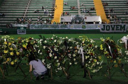 A woman places flowers before a mourning ceremony for victims after a plane carrying Brazil's soccer team Chapecoense crashed in Colombia, at Arena Conda stadium in Chapeco