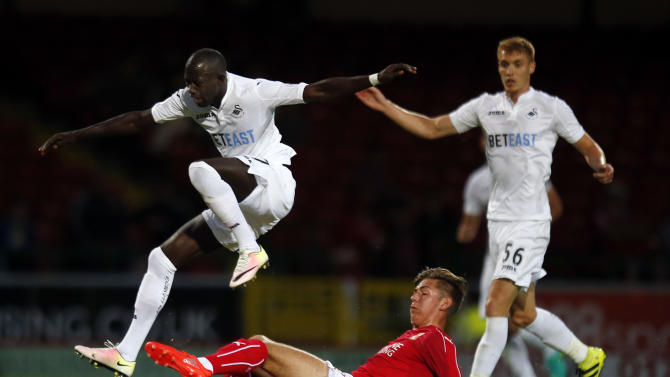Swansea City's Modou Barrow in action with Swindon's Ellis Landolo