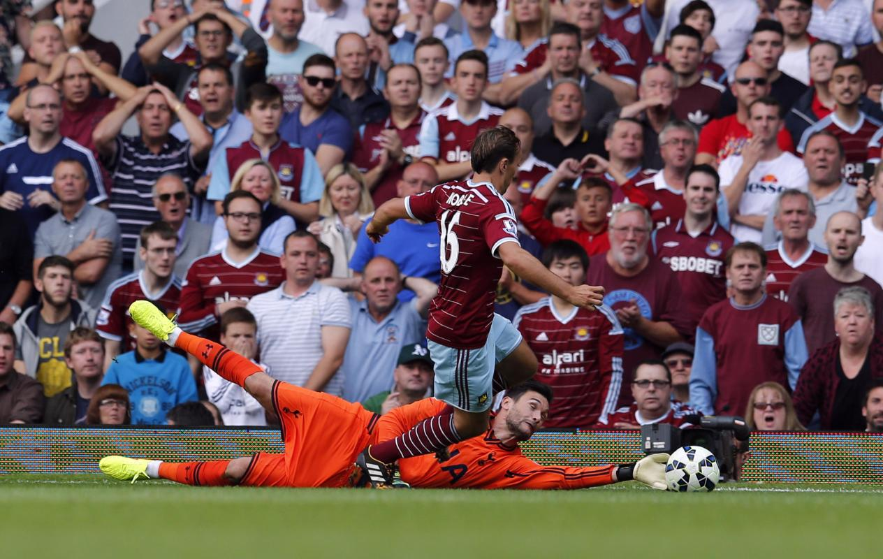 West Ham United's Noble challenges Tottenham Hotspur's goalkeeper Lloris during their English Premier League soccer match at Upton Park in...