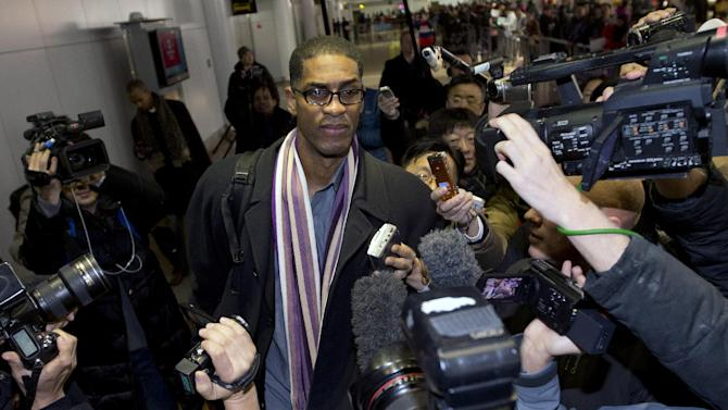 Former NBA basketball star Charles D. Smith, center, is mobbed by journalists upon arrival at the Beijing Capital International Airport in Beijing from Pyongyang, North Korea, Friday, Jan. 10, 2014. A squad of former basketball stars led by Dennis Rodman had a friendly game with North Korean basketball players in Pyongyang
