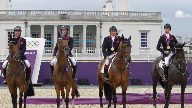 Britain's equestrian team jumping members sit on their horses with their gold medals in Greenwich Park at the London 2012 Olympic Games