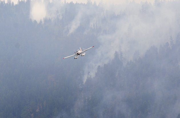 A water bomber returns to Okanagan Lake during efforts to fight the wildfire in Kelowna, B.C. (Reuters)