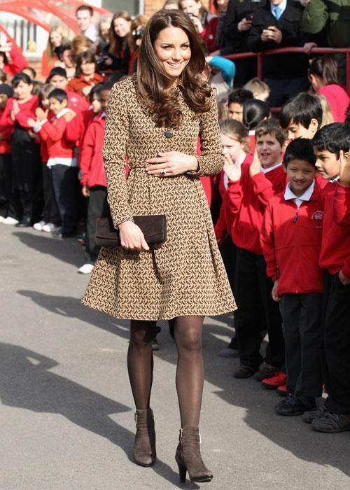 "Kate wears a $257 shirt dress by Irish designer Orla Kiely during her visit to the school on Feb. 21, 2012. Inside the classroom, Kate wore an apron that read ""Miss Catherine"" on the front. Kate wears"