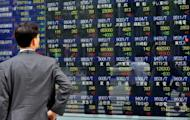 A man looks at an electronic share prices board in Tokyo. Asian markets rose for a second straight day on Tuesday as dealers picked up bargains after heavy selling through May, with confidence boosted by hopes that Greece will avoid exiting the eurozone