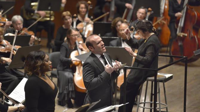 """In this April 8, 2013 photo provided by Opera Orchestra of New York, tenor Michael Fabiano, center, performs the role of Oronte in Opera Orchestra of New York's concert performance of Verdi's """"I Lombardi"""" at Avery Fisher Hall in New York. At left is soprano Courtney Johnson in the role of Oronte's mother, Sofia, with Eve Queler conducting the orchestra.(AP Photo/Opera Orchestra of New York, Stephanie Berger)"""