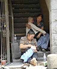 Two women care for their children at the entrance of their home in Yiliang on September 8. Many residents boarded coaches heading to the nearby city of Zhaotong while others left for nearby Yiliang City, which has become a safe haven for rootless, shell-shocked families