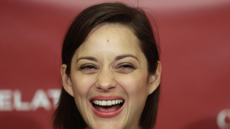 Hasty Pudding Woman of the Year, actress Marion Cotillard, of France, laughs during a news conference at Harvard University, in Cambridge, Mass., Thursday, Jan. 31, 2013. The award was presented to Cotillard by Hasty Pudding Theatricals, a theatrical student society at Harvard. (AP Photo/Steven Senne)