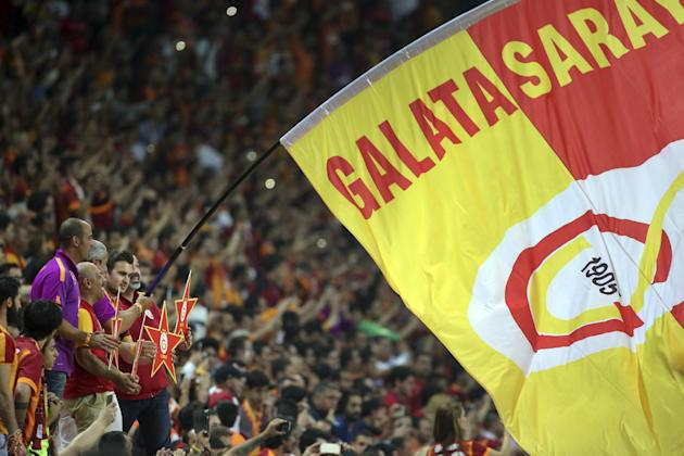 In this Sunday, May 24, 2015 photo, Galatasaray fans celebrate their team's 2-0 victory against Besiktas following their Turkish League derby soccer match at Turk Telekom Arena in Istanbul, Turkey