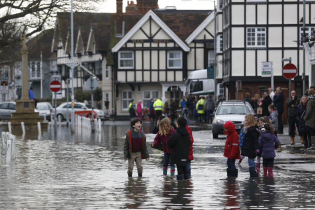 Children react in a flooded street, in Datchet, England, Monday, Feb. 10, 2014. The River Thames has burst its banks after reaching its highest level in years, flooding riverside towns upstream of Lon