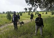 Mexican police officers look for evidence in the surroundings of a park in the municipality of Tlalmanalco, some 30 km southeast of Mexico City on August 22, 2013, where at least 7 bodies were discovered in a mass grave