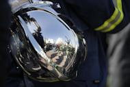 Firefighters as reflected on a firefighter helmet during a protest outside parliament amid a contract dispute with the cash-strapped government, in Athens on Thursday, Feb. 16, 2017. The government says it is lacking the funds needed to offer thousands of firefighters long-term contracts. Greece is under pressure to make deeper spending cuts as it struggles to reach agreement with bailout lenders on the terms of future loan payouts. (AP Photo/Thanassis Stavrakis)