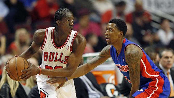 Chicago Bulls forward Tony Snell, left, looks to pass the ball against Detroit Pistons guard Kentavious Caldwell-Pope, right, during the first half of an NBA basketball game in Chicago, Saturday, Dec. 7, 2013