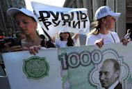 Members of a pro-Vladimir Putin group at a rally in Moscow on August 17, 2011 carry an imitation banknote with a picture of Putin