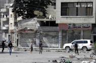 Image released by the Syrian opposition Shaam News Network shows UN monitors in Homs' Khalidiyah neighbourhood, May 22. Syrian forces tried to storm the rebel bastion of Rastan, reports said. AFP is using pictures from alternative sources as it was not authorised to cover this event and is not responsible for any alterations which cannot be independently verified