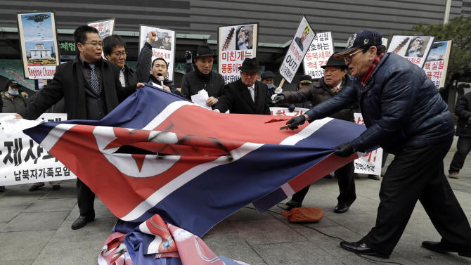 "South Korean protesters slit up a North Korean flag during an anti-North Korea rally in Seoul, South Korea, following a nuclear test conducted by North Korea Tuesday, Feb. 12, 2013. North Korea said it successfully detonated a miniaturized nuclear device at a northeastern test site Tuesday, defying U.N. Security Council orders to shut down atomic activity or face more sanctions and international isolation. The signs read "" Out, Kim Jong Un."" (AP Photo/Lee Jin-man)"