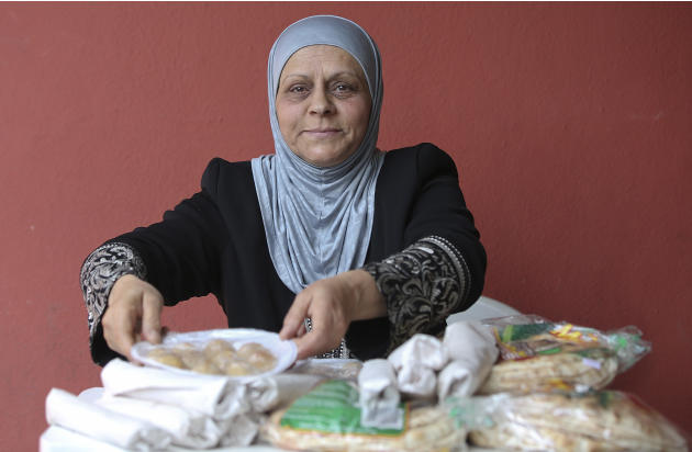 In this May 15, 2015 photo, Syrian refugee Dalaz Chora sells Arabic food outside a mosque in Sao Paulo, Brazil. Brazil's National Committee for Refugees said around 1,900 Syrian refugees have arrived