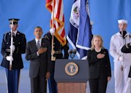 "US President Barack Obama and Secretary of State Hillary Clinton listen to the National Anthem during the transfer of remains ceremony marking the return to the US of the remains of the four Americans killed in an attack this week in Benghazi, Libya, at the Andrews Air Force Base in Maryland. Clinton said their deaths were ""senseless"" and ""unacceptable."""