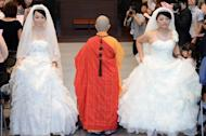 Taiwanese women Fish Huang (right) and her partner You Ya-ting attend their same-sex Buddhist wedding ceremony in Taoyuan. The two women tied the knot on August 11 in Taiwan's first same-sex Buddhist wedding, a move rights groups hope will help make the island the first society in Asia to legalise gay marriage