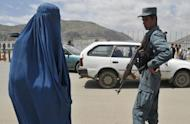 A burqa-clad Afghan woman walks past a policeman at a checkpoint in Kabul last week. The upcoming NATO summit in Chicago must ensure that special measures are taken to protect the rights of Afghan women as US-led coalition forces prepare to pull out, UN organisations said Saturday