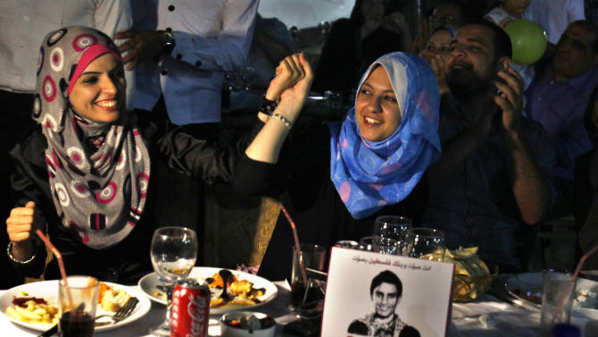 "Palestinians dance and sing while watching the televised performance of Mohamm3d Assaf, 23, a Palestinian finalist on the Arab Idol talent show, in Gaza City, Friday, June 21, 2013. Assaf, Gazan's powerful voice has propelled him to the final at the ""Arab Idol"" in a TV talent contest choosing a winner in Beirut on Saturday. He is the first Palestinian to qualify for ""Arab Idol"". Arabic on the sign on the table reads ""Vote to the son of Palestine NO. 3"" and ""Vote and the Bank of Palestine votes with you."" (AP Photo/Adel Hana)"