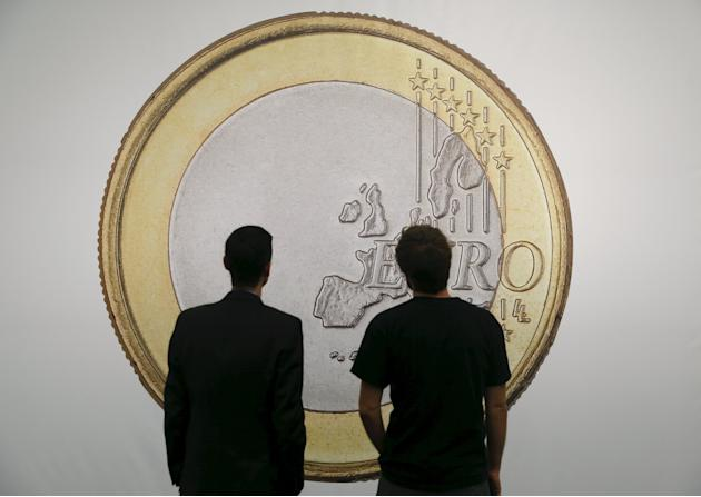 Men are silhouetted against a photo print of a huge Euro coin at the 49th Art Cologne fair in Cologne