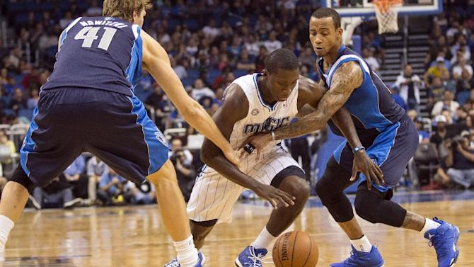 Dallas Mavericks' Dirk Nowitzki, left, and Monta Ellis, right, fight for the ball with the Orlando Magic's Victor Oladipo, center, during the first half of an NBA basketball game in Orlando, Fla., Saturday, Nov. 16, 2013