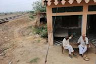 Two men sit near dried out fields in the village of Kherikhummar, in northern India in July 2012. India's economic growth could slip to near six percent this year with the country facing the spectre of its third drought in a decade, a top government policymaker says