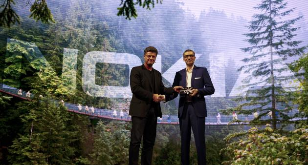Suri, Nokia's President and Chief Executive Officer, is greeted by Nummela, Chief Executive Officer of Nokia-HMD, during a ceremony at Mobile World Congress in Barcelona
