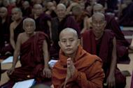 Wirathu (C), a Buddhist monk from Mandalay whose anti-Muslim remarks have come under recent scrutiny, attends a conference about religious violence in the country, at a monastery near Yangon, on June 13, 2013. Opposition leader Aung San Suu Kyi has criticised a proposal by Wirathu to restrict marriages between Buddhist women and men of other faiths, describing it as a violation of human rights