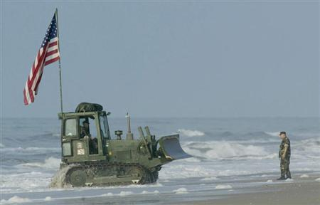 A bulldozer makes its way onto Onslow beach at Camp Lejeune, North Carolina, May 26, 2003 after being unloaded from a landing craft. REUTERS/Ellen Ozier