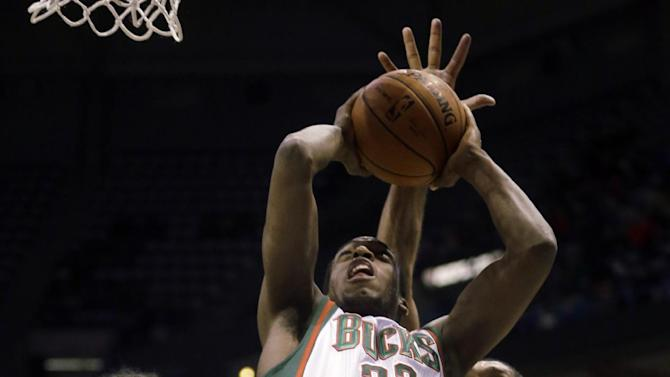 Milwaukee Bucks' Khris Middleton(22) has his shot blocked as he goes up against San Antonio Spurs' Tim Duncan (21) and Kawhi Leonard during the first half of an NBA basketball game Wednesday, Dec. 11, 2013, in Milwaukee