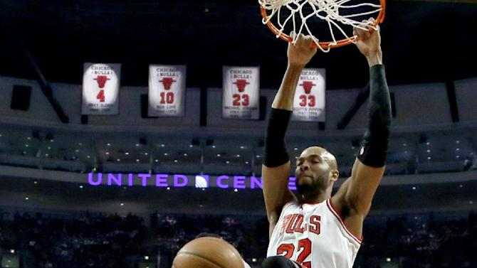Chicago Bulls power forward Taj Gibson (22) dunks between Boston Celtics power forward Kris Humphries, left, and Kelly Olynyk (41) during the first half of an NBA basketball game on Thursday, Jan. 2, 2014, in Chicago