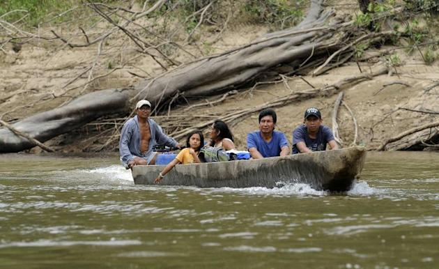 Ecuadorean Huaorani natives cross the Tiputini river at the Yasuni National Park, at the Ecuadorean Amazon forest, on August 21, 2010