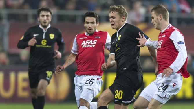 Anzhi Makhachkala's Aleksandr Bukharov fights for the ball with AZ Alkmaar's Jeffrey Gouweleeuw and Celso Ortiz during their Europa League soccer match in Alkmaar
