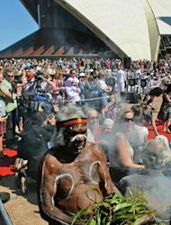 Aboriginal elder (C) performs a smoking ceremony on the steps of the Sydney Opera House as the world heritage-listed building celebrates its 40th birthday, on October 20, 2013
